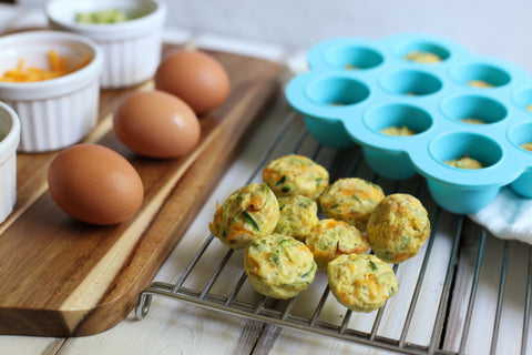 Egg and broccoli fritters with silicone freeze tray in the back also eggs and ramekins