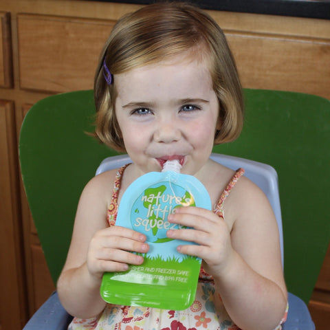 Girl toddler using a reusable food pouch