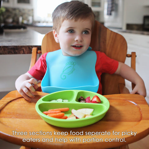 young boy eating from a green silicone divided toddler plate