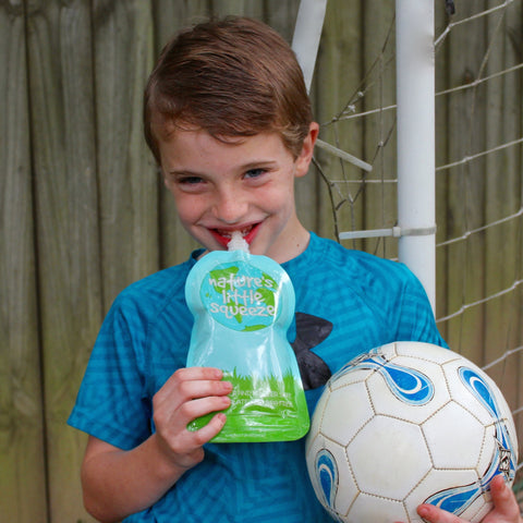 Boy holding a soccer ball eating from a reusable food pouch