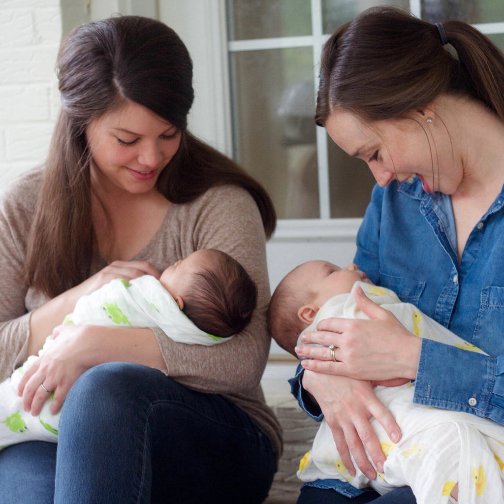Mothers holding swaddled babies