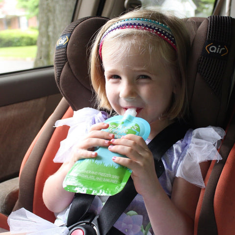 Girl child eating from reusable food pouch