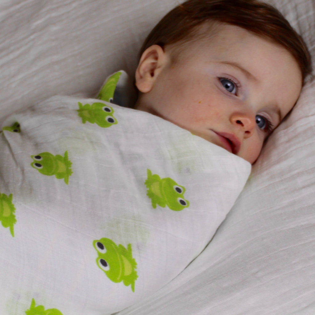 Baby swaddled in a frog imprinted organic cotton blanket