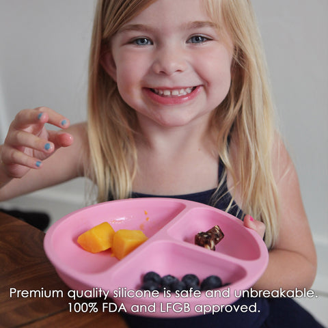 Young Girl eating off of a pink divided silicone plate for toddlers