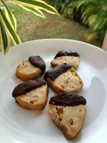 mac nut shortbread cookies dipped in chocolate on white plate