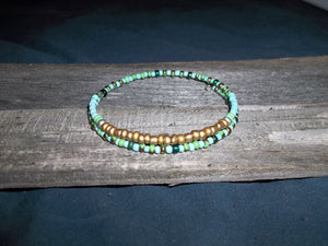 "A mix of Turquoise and glass beads, with a focal point of gold matte beads across the top, this stackable bracelet can be worn with many different bracelets or alone depending on your mood and style.  Makes a great gift idea for any occasion and a great addition to any ladies jewelry wardrobe.  This bracelet is plus size and is made with 75mm stainless steel memory wire.  SIZE:  XXL  ( FITS 8""- 9,5"" WRIST) ARTISAN:  Kat Salinas"