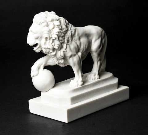 Small marble replica lion in St. Augustine, Florida orb on right side full view on left side