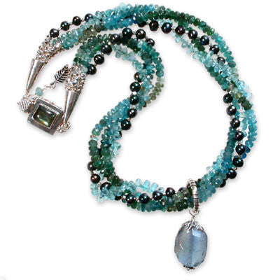 4-strand necklace of varigated apatite rondelles and tiny aqua apatite faceted teardrops with a large fluorite pendant