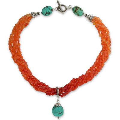 torsade of 6 strands of ombre carnelian flat rounds & 1 strand of ombre faceted carnelian rondelles with a large turquoise stone pendant & turquoise stone closure