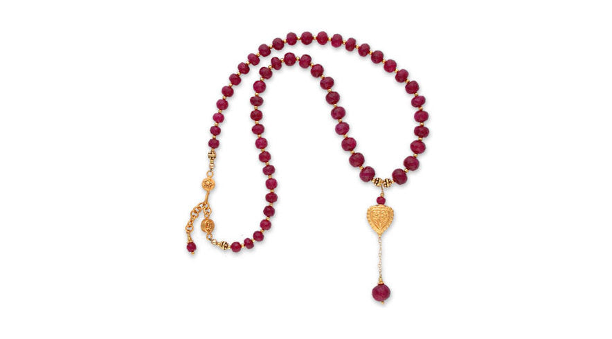 sparkling faceted ruby briolette & heart-shaped repousee' bead on a graduated strand of sparkling faceted rubies.