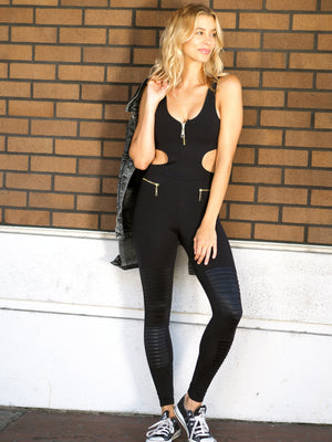 woman in black jumpsuit. catsuit. bodysuit. yoga clothing. wearing black jumpsuit with converse sneakers