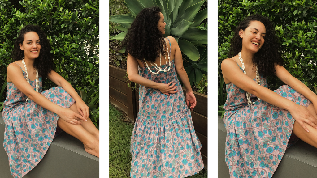 The beautoful Tonganese Mailianive, poses in three different positions, in her garden, wearing the Boom Shankar Sitar Dress in the Rose Quartz design