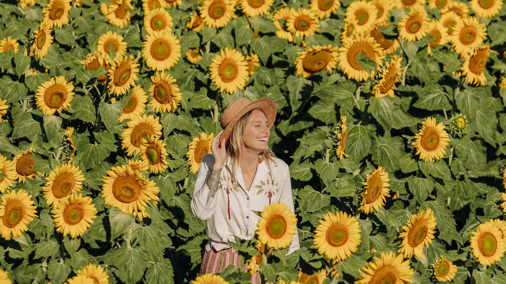 Sweet blonde girl in a straw hat stands in the middle of a field of sunflowers