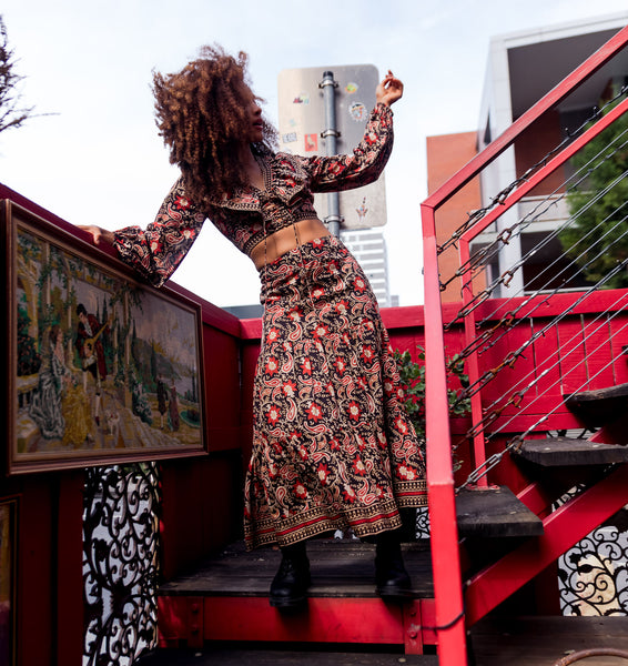 Sophia standing on a staircase wearing a matching block print crop top and long skirt