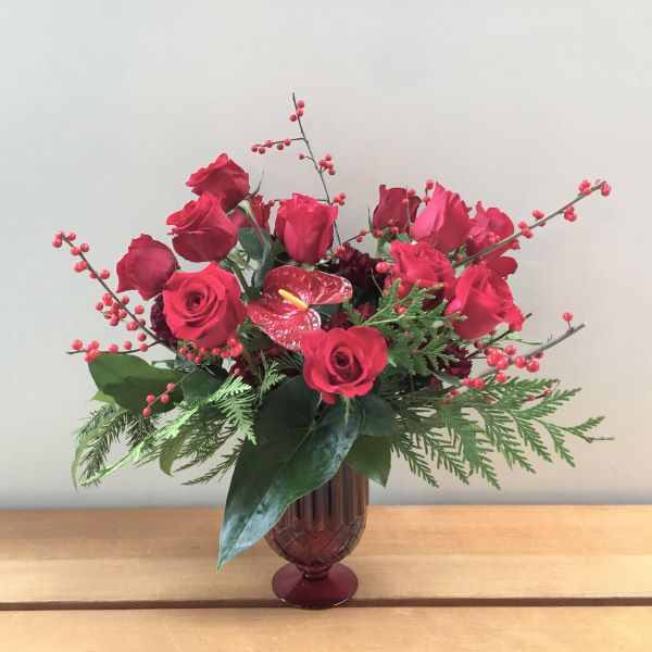 Christmas arrangement with 12 red roses, deep burgundy carnations, a red anthurium, ilex berries and evergreen, all displayed beautifully in a red glass vase.,