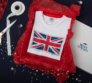 Teddy Edward Union Flag white T-Shirt inside gift box wrapped in red tissue paper, surrounded by ribbon, baubles and sparkles.