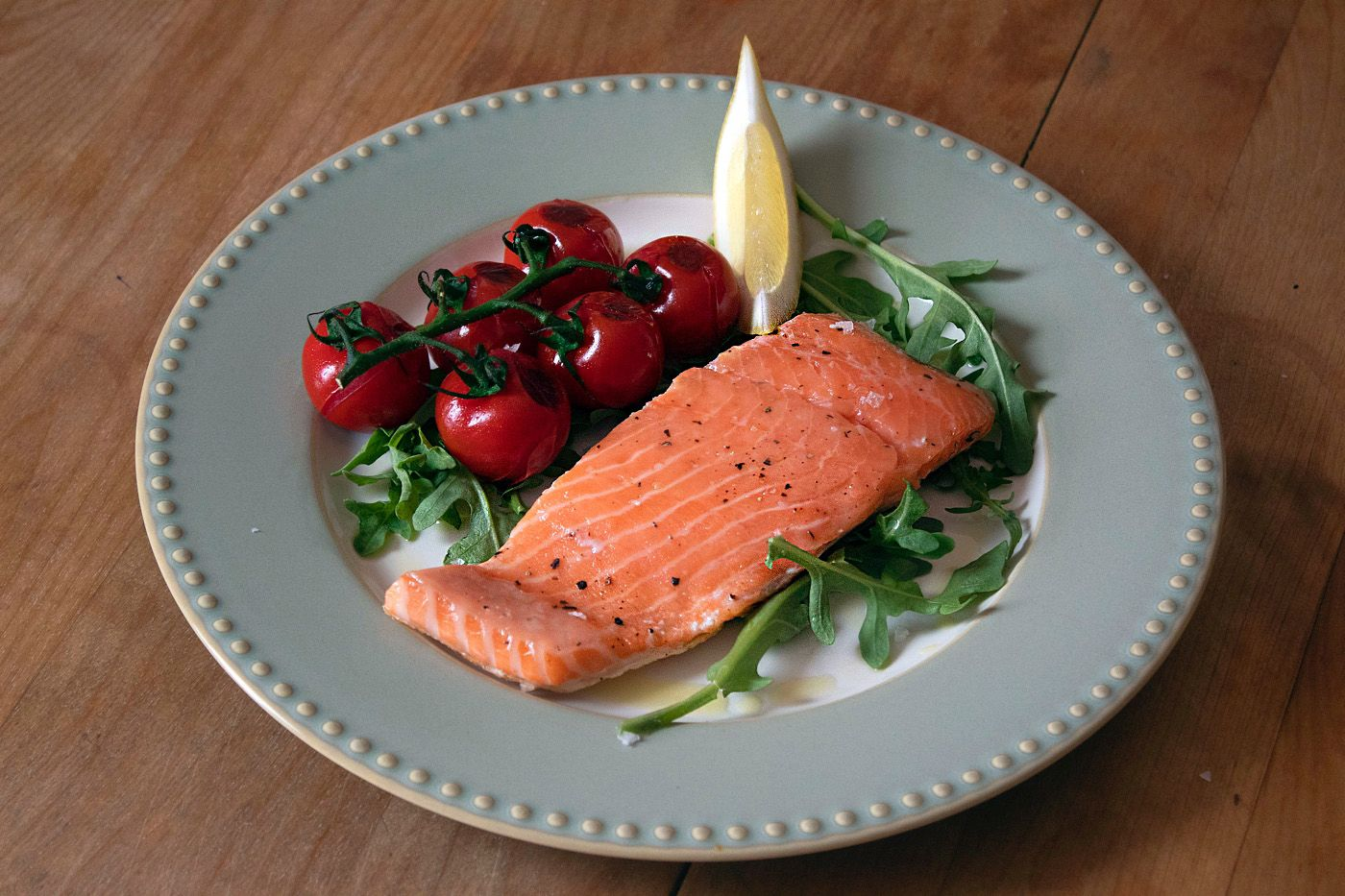 Salmon Fillet with Blistered tomatoes and crispy skin cooked on cinder grill using precise cooking