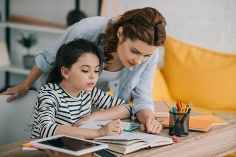 A mother homeschooling her daughter through the use of a positive behavior chart for home.
