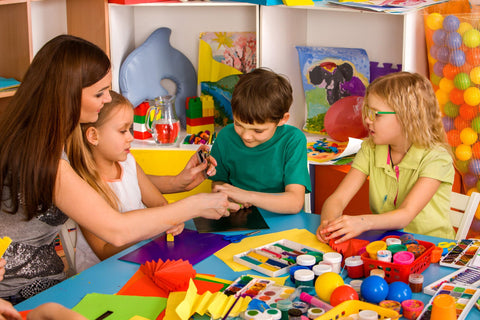 Children practicing social-emotional learning in the classroom by playing creatively.