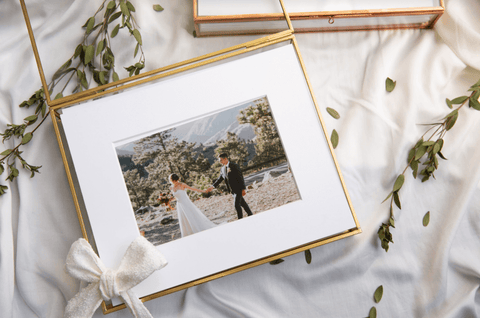 Glass photo box with gold rim set on a white sheet surrounded by dried leaves. The photo box holds a beautiful fine art printed photo inside of an archival hinged photo mat.