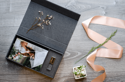 A dark gray linen photo box with a fine art printed photo and custom glass USB Flash Drive inside. Next to the box is a pink satin ribbon and dried flowers.