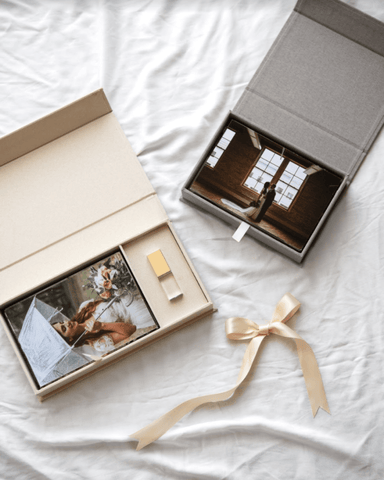 One cream linen photo box that houses fine art printed photos and a crystal glass USB Flash Drive next to a smaller, gray linen photo box.