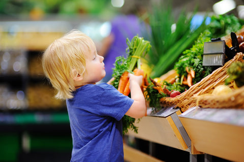 Cute toddler shopping for organic carrots - this week's Living Juice ingredient spotlight