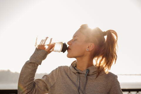 Young woman drinking water - blog by O2 Living makers of living health and wellness cbd and hemp extract