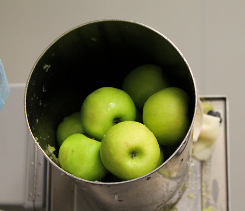 Organic, green apples being juiced for Living Juice's organic, cold-pressed fruit and vegetable juices