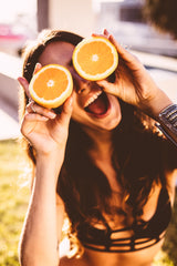 Girl in summer eating oranges - O2 Living blog by makers of organic cold pressed Living Juice