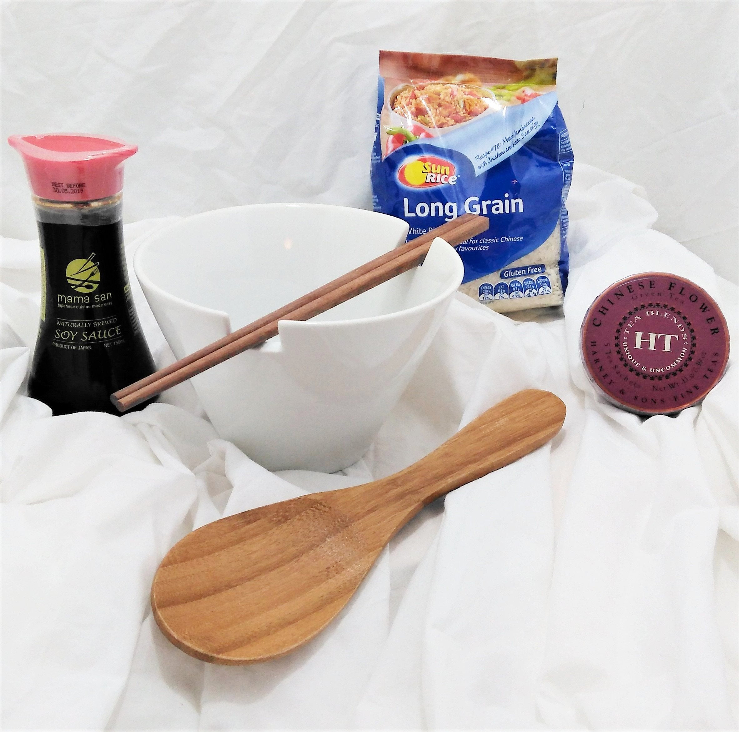 Oriental rice bowl gift - a 15 cm white procelain rice bowl with chopsticks that rest in the bowl cut-outs, Chinese flower green tea, bamboo rice spoon, soy sauce and long grain rice