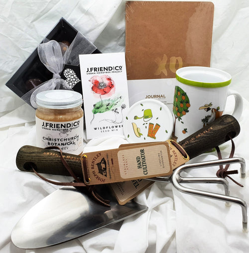 Gardener gift with quality hand trowel and cultivator set, honey, wildflower seeds, journal, chocolate selection and beautiful garden themed tea mug infuser set.