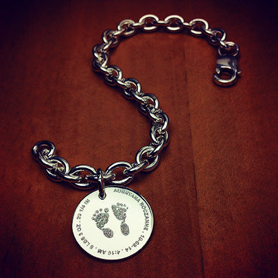 Women's charm bracelet custom engraved with real baby footprints and birth details. Gift for a new mother
