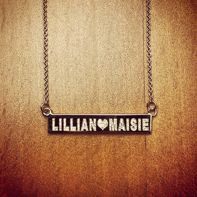 Gold horizontal bar necklace custom engraved with etch-filled names and a heart