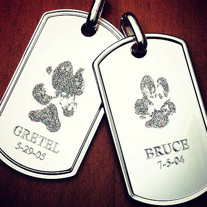 Sterling silver dog tags custom engraved with pet dog's paw-prints.