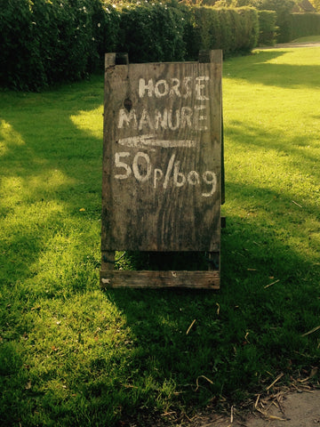 A roadside sign advertising horse manure