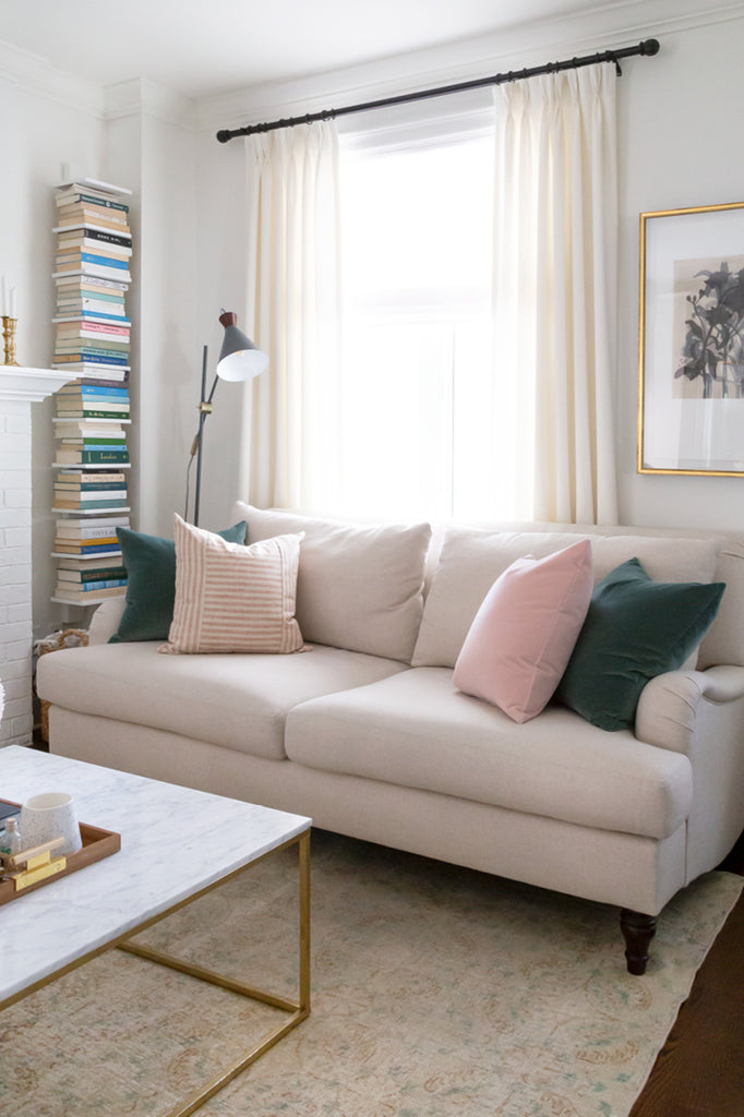 Adena Leigh's neutral living room with Tonic Living pillows, roll-arm sofa, ivory drapes and book nook