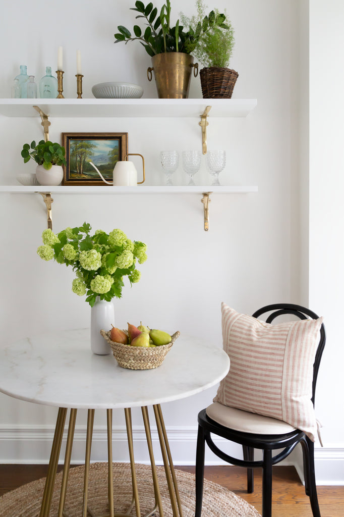 Adena Leigh's breakfast nook with marble bistro table and floating shelves