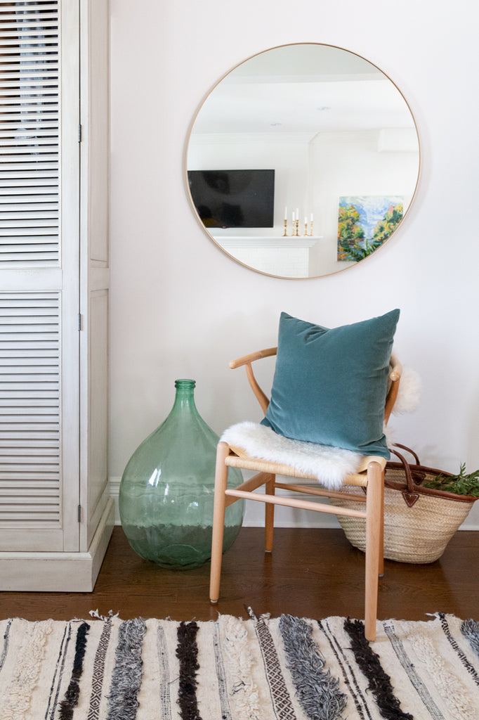 Adena Leigh's open-concept entryway with wishbone chair, round brass mirror and Tonic Living pillows