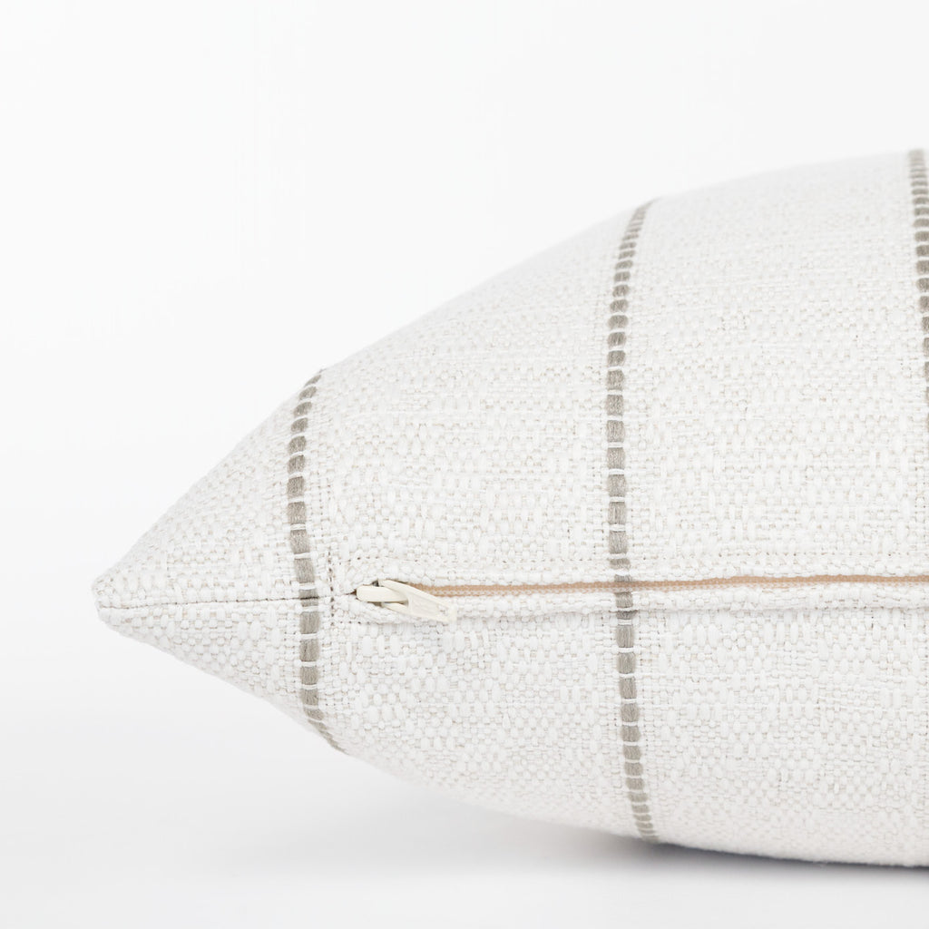 Toulouse, Cotton - A textured, creamy white lumbar pillow with vertical taupe grey stripes in a thin stitched line.