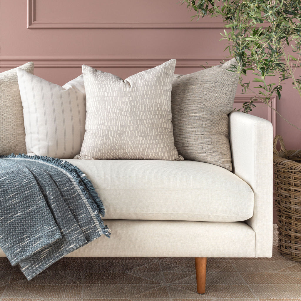Cream sofa neutral pillow combo: Avareno Silver, Farina Birch, Stanhope Ash pillows with Rafael Stone Blue cotton throw