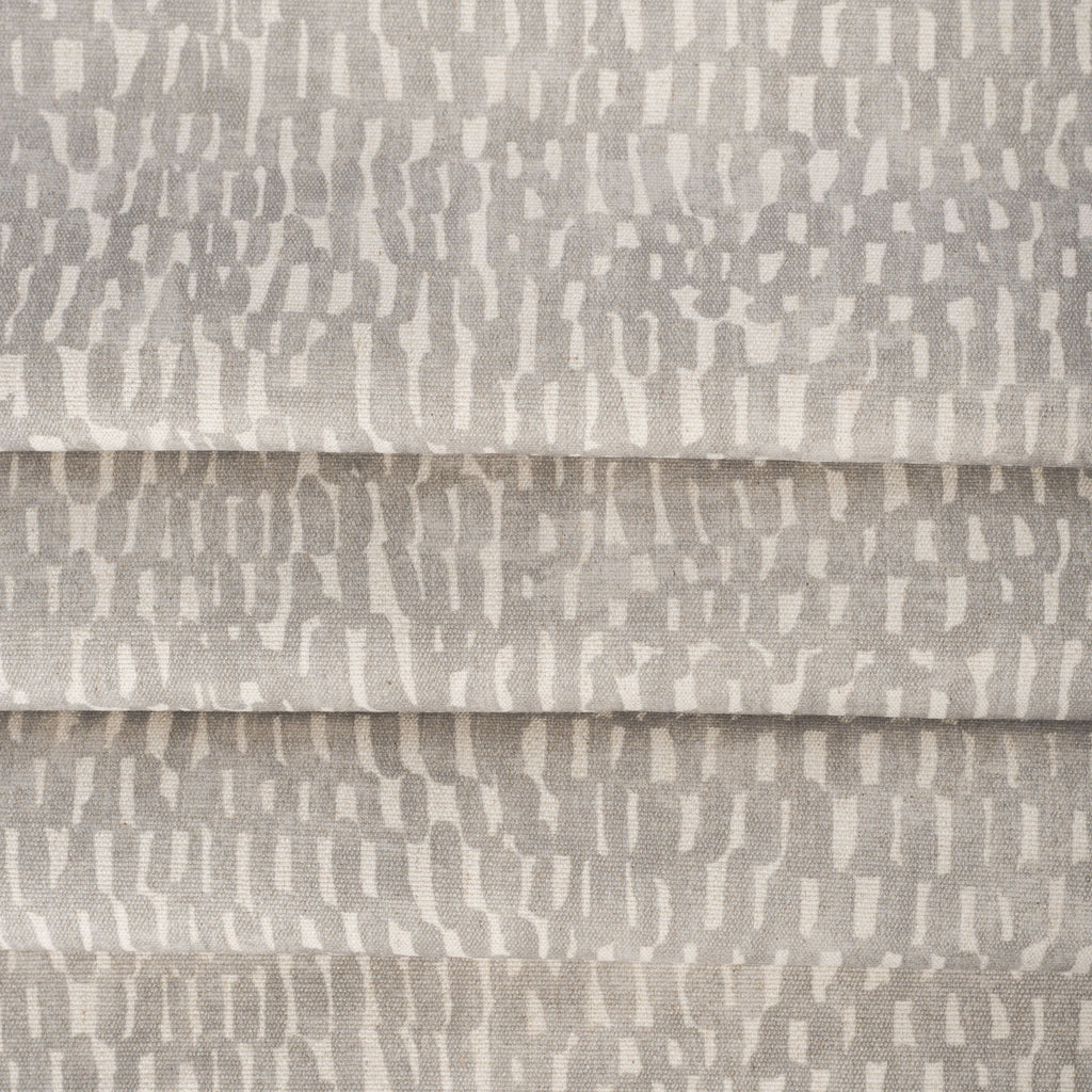 Avareno Silver, a light gray and sandy beige small scale abstract print fabric : close up with soft folds