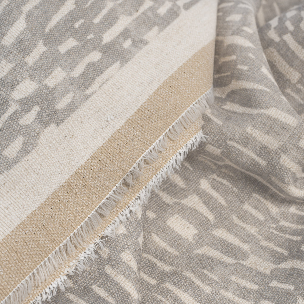 Avareno Silver, a light grey and sandy beige small scale abstract print fabric : close up selvage edge