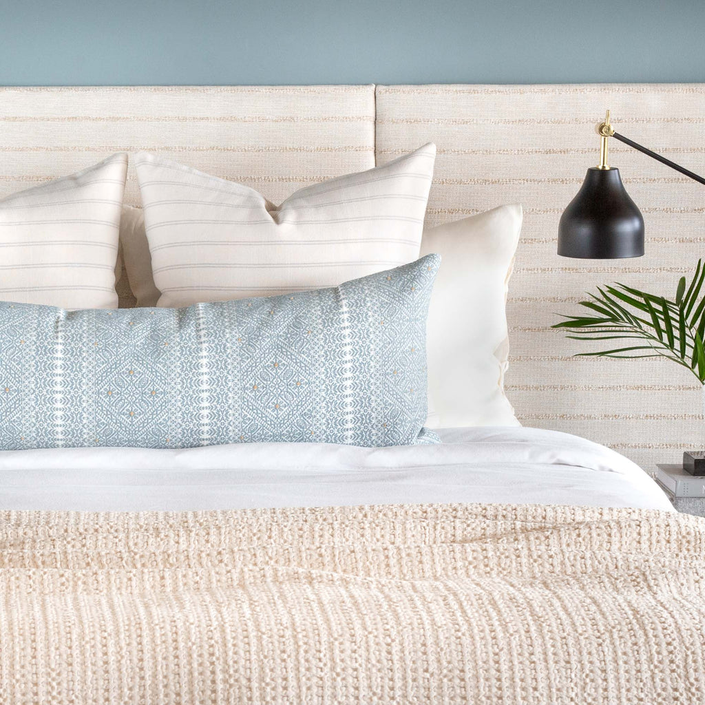 Bed vignette: Delilah pale blue lace pattern bolster bed pillow and Farina stripe pillows