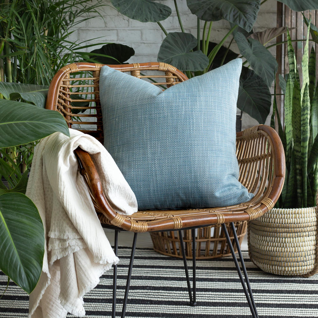 Ernesto Riviera, a textured stone blue indoor outdoor pillow on a rattan chair surrounded by plants