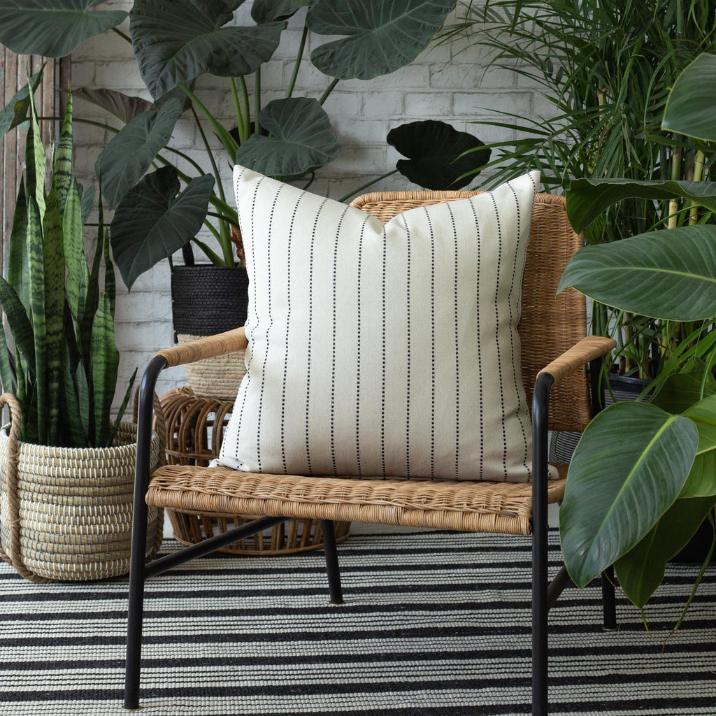 Outdoor patio vignette: cream and black indoor pillow, rug and plant baskets from Tonic Living