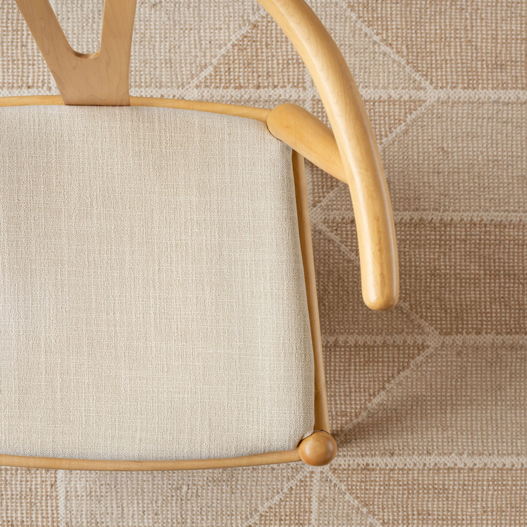 Grange Fabric Parchment, a high performance sandy beige upholstery fabric shown on a chair seat