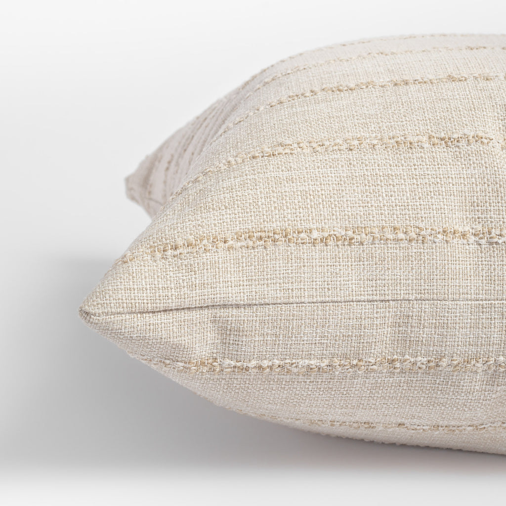 close up view of a creamy beige pillow with tonal textured stripe