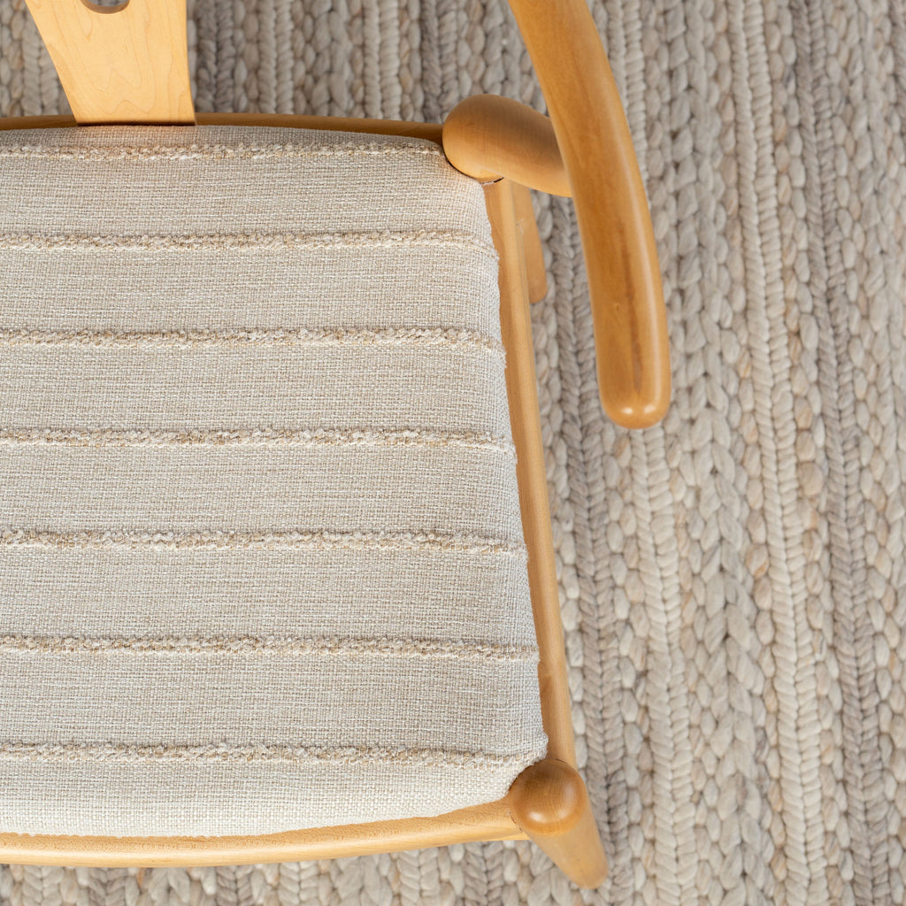 Handlavet Raffia textured stripe fabric shown on an upholstered chair seat
