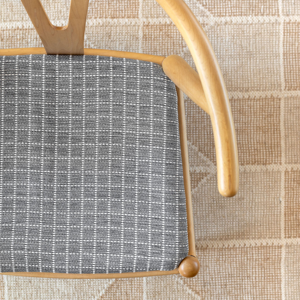 Keely Check stone gray and off-white texture stitched windowpane pattern upholstery fabric shown on a chair seat